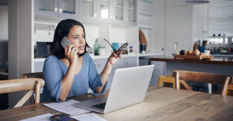 woman at home on smartphone while looking at laptop